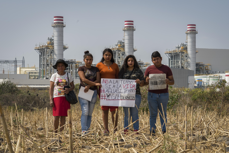 Miembros del movimiento Huexca en Resistencia muestran una pancarta contra la central termoeléctrica construida en la comunidad.