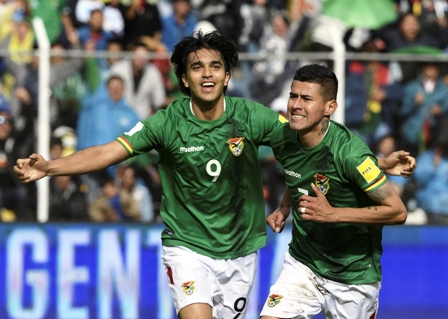 Bolivia's midfielder Juan Arce (R) celebrates with teammate Marcelo Martins after scoring a goal against Argentina during their 2018 FIFA World Cup Russia South American qualifier football match at Hernando Siles stadium in La Paz, Bolivia, on March 28, 2017. / AFP PHOTO / JUAN MABROMATA