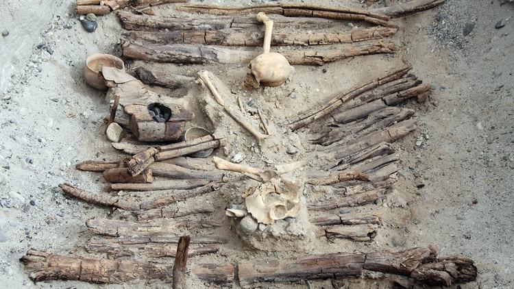 Braseros de madera y un esqueleto encontrado en la tumba M12, tal como quedaron expuestos en las excavaciones de un sitio arqueológico en el oeste de China que proporcionó evidencia sobre la quema de marihuana en un cementerio hace unos 2.500 años (Xinhua Wu/Handout via REUTERS)