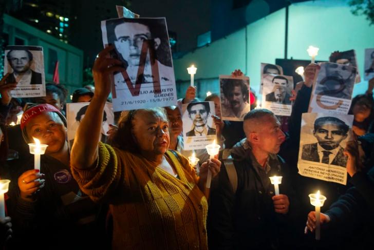 En esta fotografía del 5 de agosto de 2019, manifestantes sostienen fotos de las personas asesinadas durante la dictadura de Brasil afuera de una estación policial que era un centro de tortura en la dictadura en Sao Paulo, Brasil. (AP Foto/Andre Penner, Archivo)