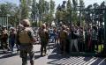 Una policía militar hace guardia en un supermercado mientras los clientes esperan en la fila, en Santiago, Chile, este lunes 21 de octubre (AP)