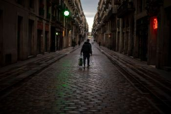 A man walks a long an empty street in downtown Barcelona, Spain, Thursday, March 26, 2020. The new coronavirus causes mild or moderate symptoms for most people, but for some, especially older adults and people with existing health problems, it can cause more severe illness or death. (AP Photo/Emilio Morenatti)