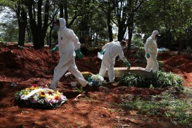 Gravediggers wearing protective suits are seen as one of then tightens a screw on the coffin of someone who died suspected to have had coronavirus disease (COVID-19), at Vila Formosa cemetery, Brazil's biggest cemetery, in Sao Paulo, Brazil, April 2, 2020. REUTERS/Amanda Perobelli