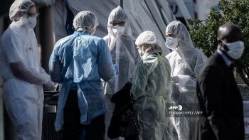 Medical personnel tend to a woman (3rdR) at the emergency entrance set up under a tent in the courtyard of the Henri Mondor Hospital in Creteil, in the suburbs of Paris on April 5, 2020, on the twentieth day of a lockdown in France aimed at curbing the spread of COVID-19 (novel coronavirus). (Photo by Philippe LOPEZ / AFP)