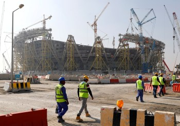 FILE PHOTO: Workers walk towards the construction site of the Lusail stadium which will be build for the upcoming 2022 Fifa soccer World Cup during a stadium tour in Doha, Qatar, December 20, 2019.  REUTERS/Kai Pfaffenbach/File Photo