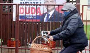 Una mujer en bicicleta pasa junto a carteles electorales para el presidente polaco Andrzej Duda, quien busca la reelección para un segundo término en comicios que aún no están seguros apenas a cuatro días de su planeada realización, en Lomianki, cerca de Varsovia, e,l miércoles, 6 de mayo del 2020. El partido de gobierno quiere que las elecciones sean aplazadas por una o dos semanas, pero la oposición pide un aplazamiento más largo. (AP Foto/Czarek Sokolowski)